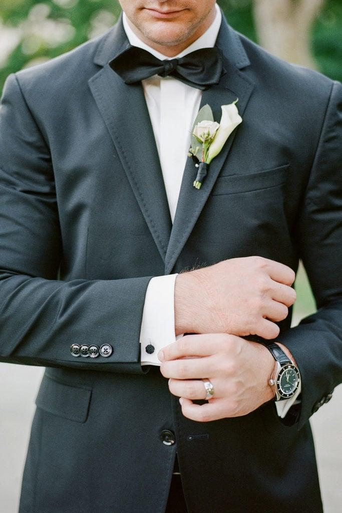 Groom fixing his cufflinks outside the Carnegie Museum Wedding Venue