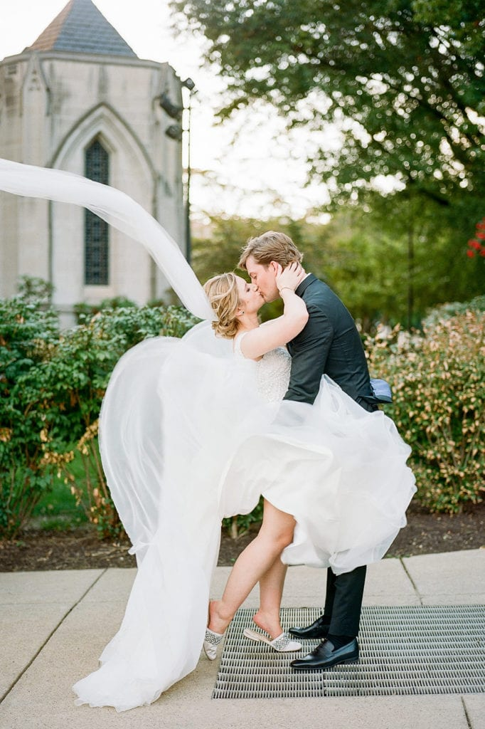 Bride and Groom portraits outside Heinz Chapel with the wind blowing wedding dress
