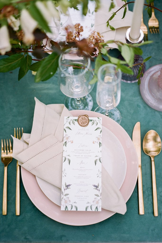 The tent merchant rentals with pink plates and gold flatware