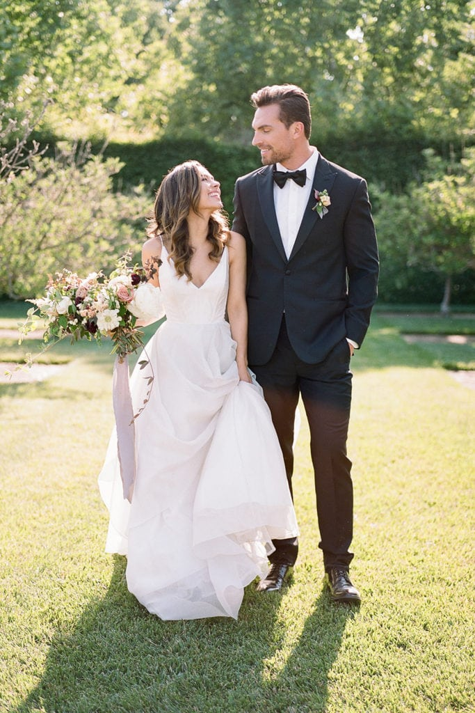 Couple walking:Ceremony Arch with flowers by Emily Reynold Design: Kestrel Park California Wedding Inspiration Styled Shoot captured by Pittsburgh Wedding Photographer Lauren Renee