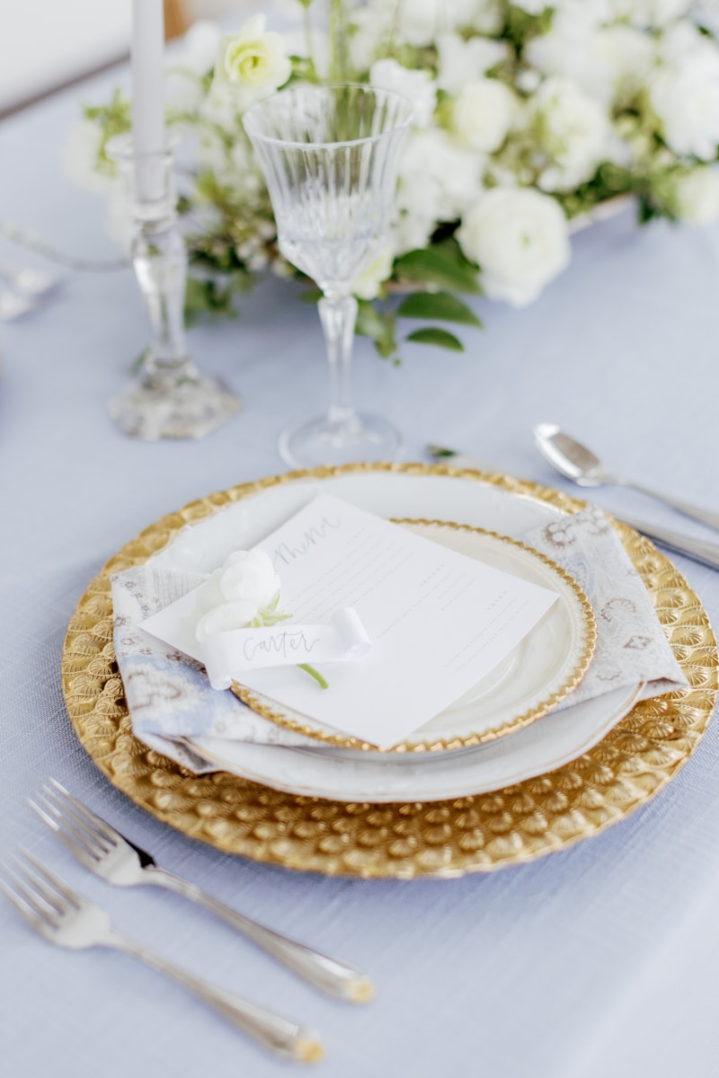 Wedding table top decor with blue linen and gold accented dishes and silverware