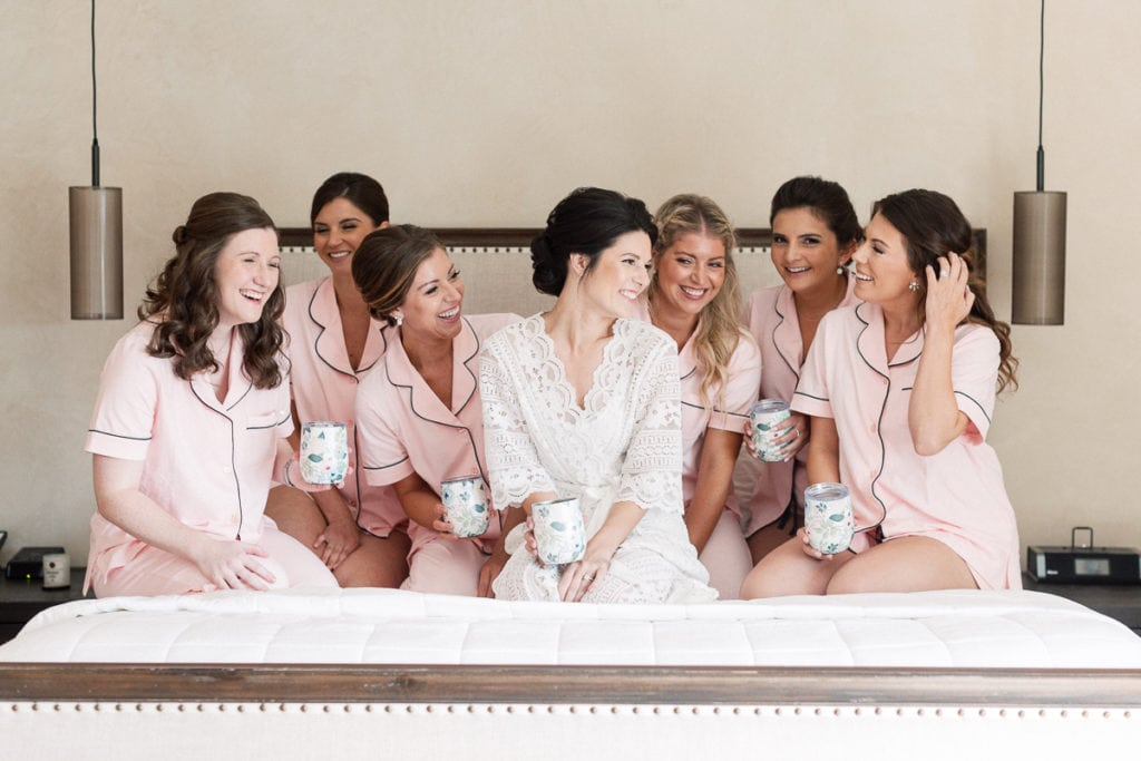 Bride with her bridesmaids sitting on a bed