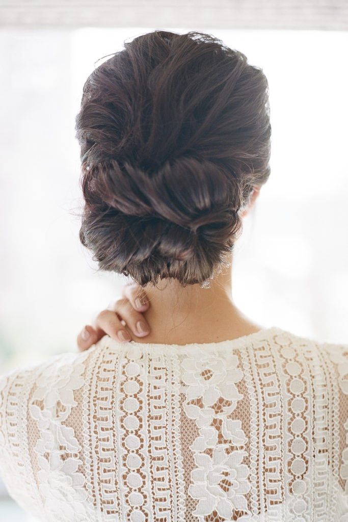 Bride wearing a lace robe while getting ready the morning of her wedding
