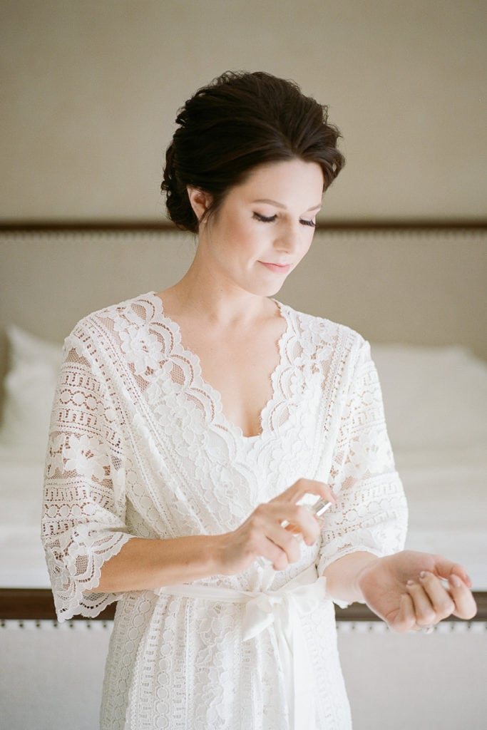 Bride putting on perfume while getting ready in her hotel suit