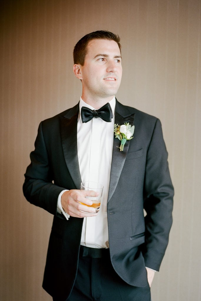 Groom holding a glass of whiskey while getting ready for his wedding