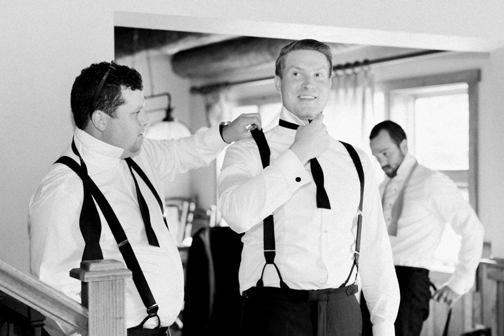 Groomsmen helping the groom get ready and tie his bowtie