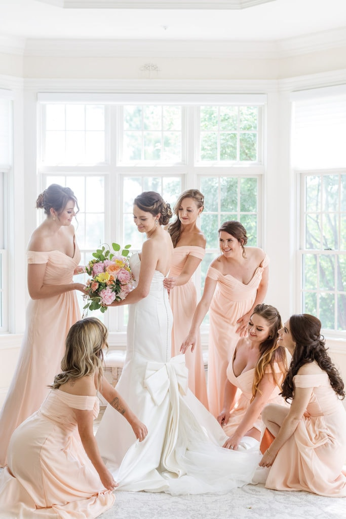 Bridesmaids in pink dresses helping with bride's bow wedding dress