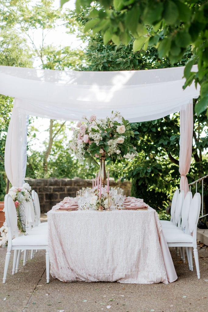 Eventioneers table rentals with white cane back chairs and a chiffon canopy with pink and mauve accents