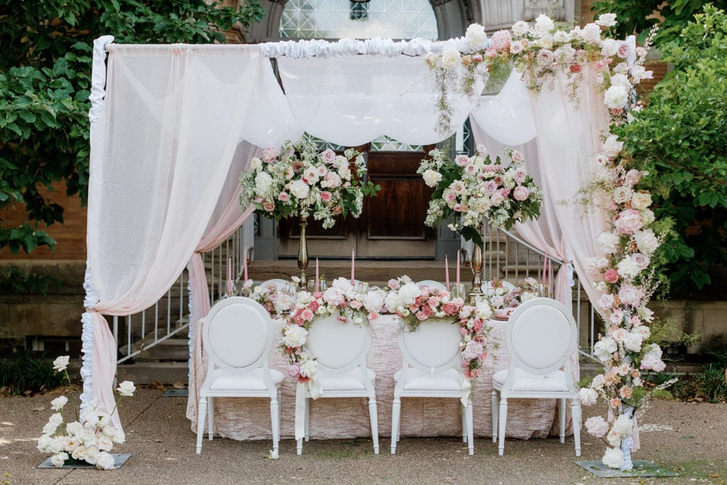 Pretty in Pink wedding inspiration table decor with cane back chairs and chiffon canopy adorned with flowers