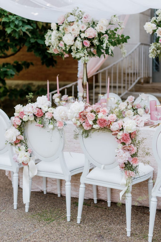 White cane back chairs decorated with pink floral crowns