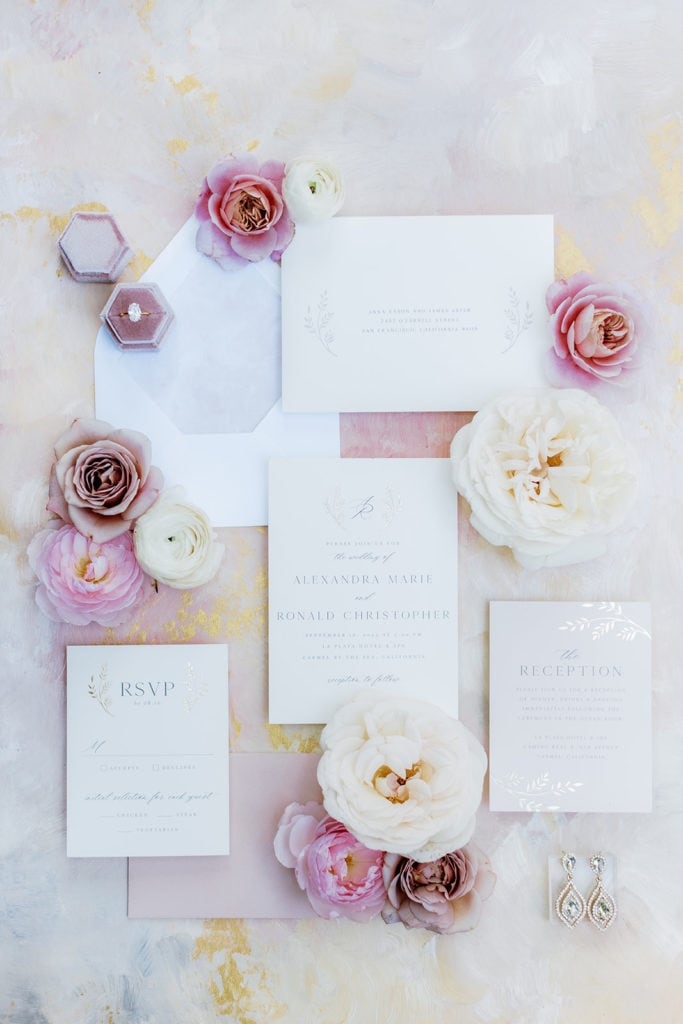 Minted wedding invitation flat lay with pink florals on Lindale Studios mat