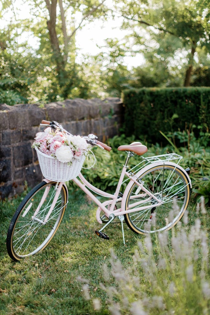 White and pink vintage Schwinn road bike with a basket of flowers