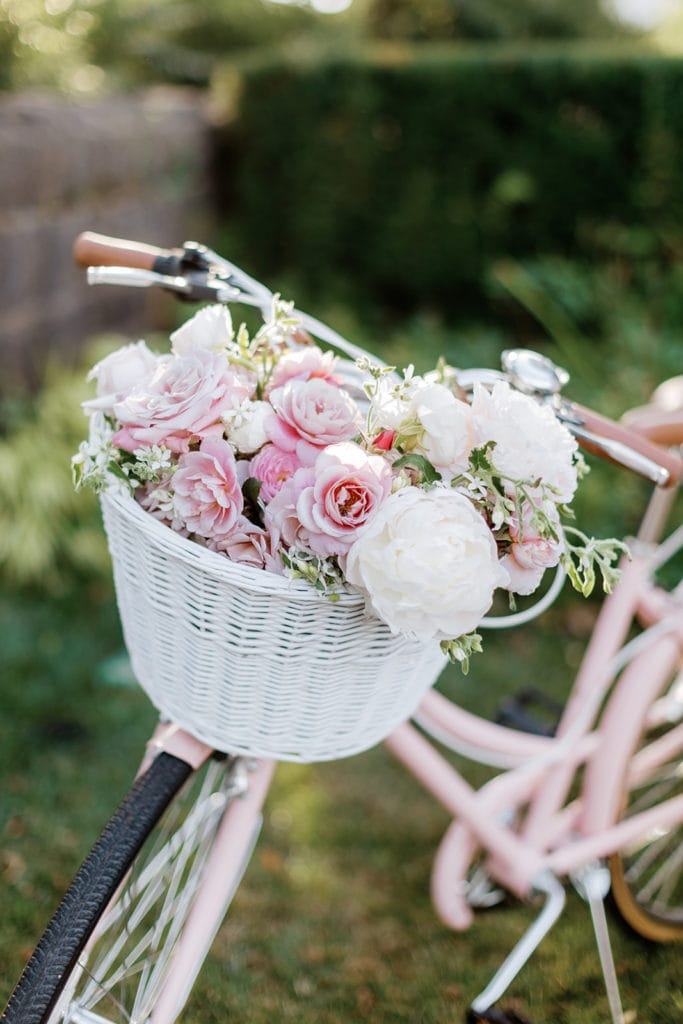 pink, white, and mauve flowers in a white bike basket in a Schwinn vintage road bike