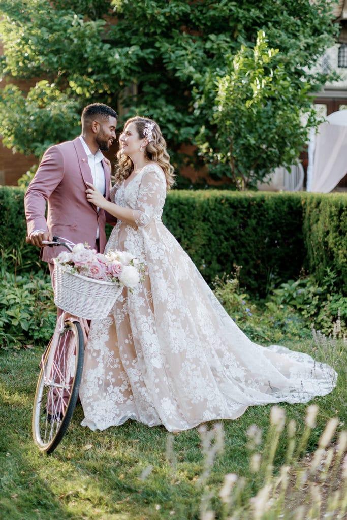 Bride and groom standing with a pink vintage Schwinn road bike