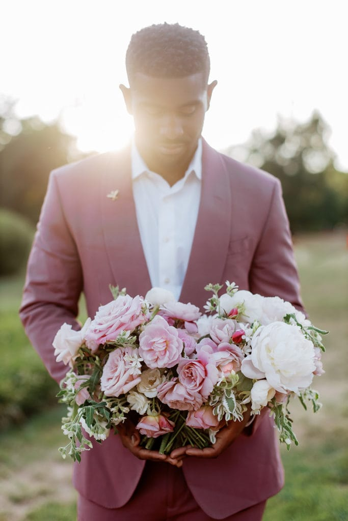 Groom in mauve tux holding pink bouquet at sunset
