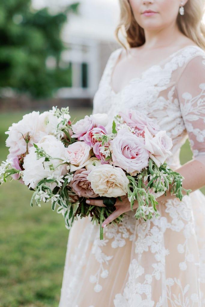 Bride holding pink, purple, and mauve colored bouquet wearing blanc de blanc bridal bouquet wedding dress