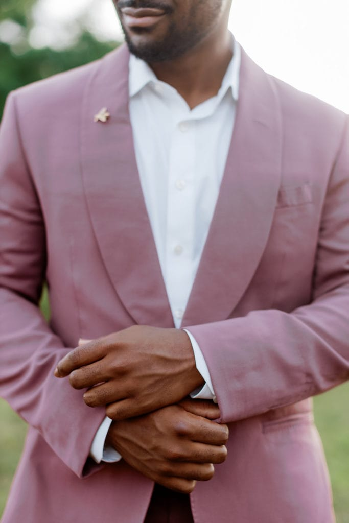 Groom fixing cufflinks of mauve and purple tux with a bumble bee lapel pin