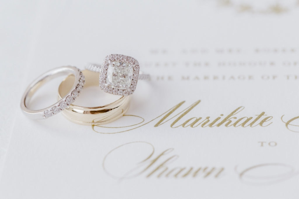 Close up photo of wedding rings on invitations by Nota Bene