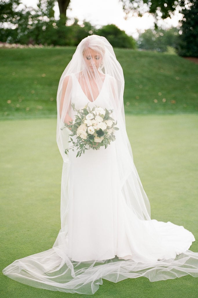 Portrait of just the bride in her watters dress and veil