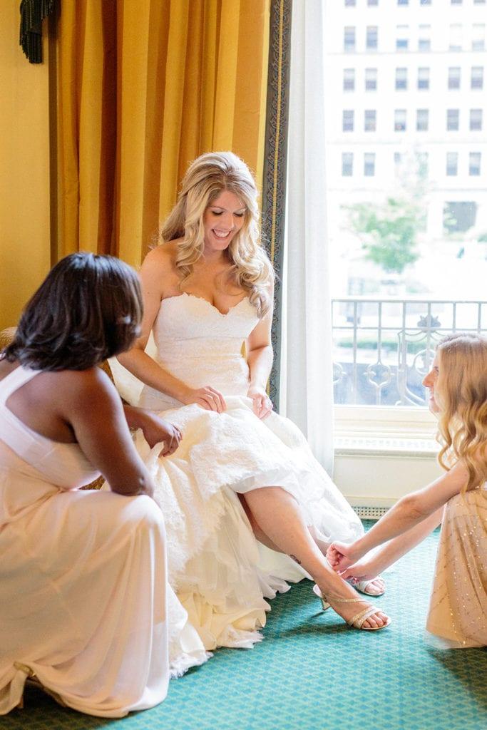 Bridesmaids helping bride put on wedding shoes