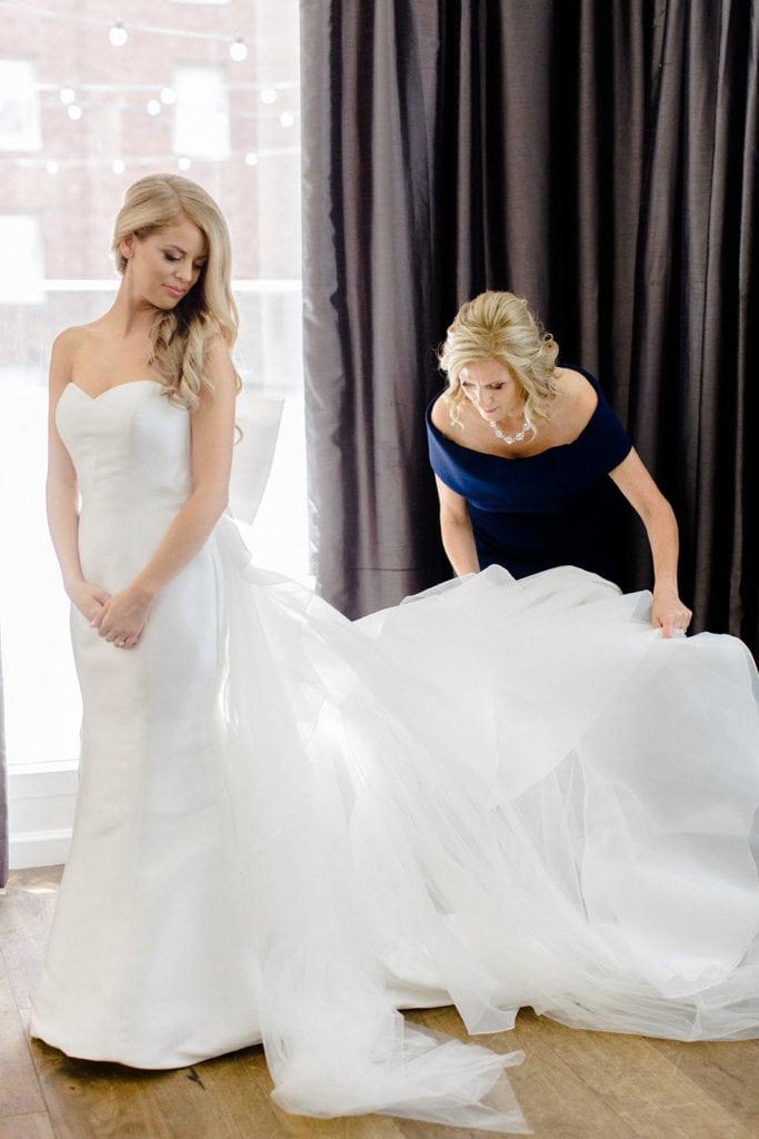 Mother of the bride fluffing bride's wedding gown captured by Lauren Renee