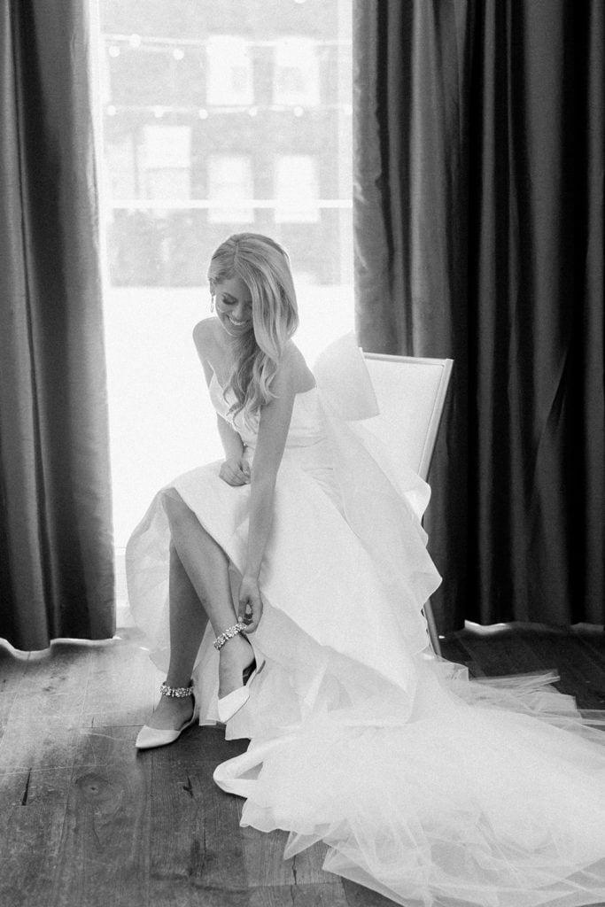Bride putting on Badgley Mischka wedding shoes