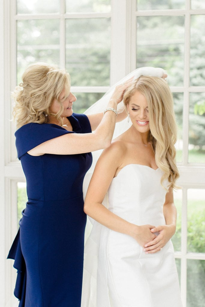 Mother of the bride placing wedding veil