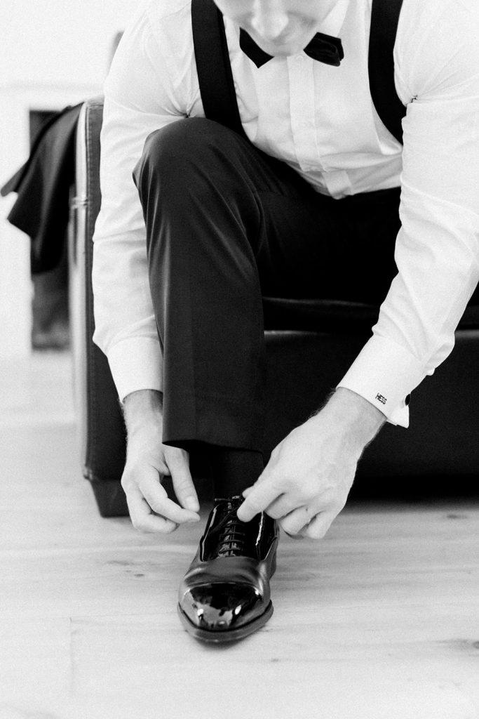 Groom tying wedding shoes