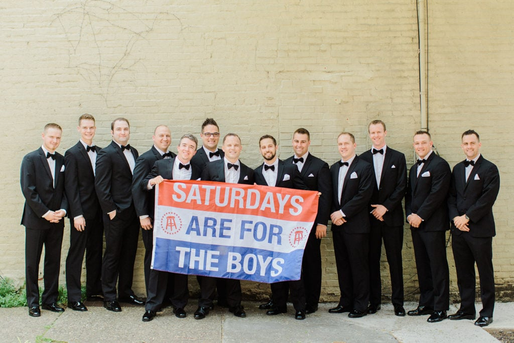 Groom and groomsmen posing with sign