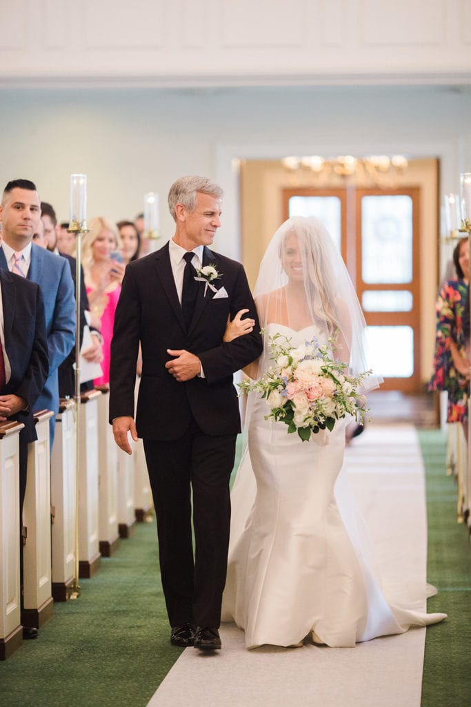 Father looking at daughter as he escorts her down the aisle