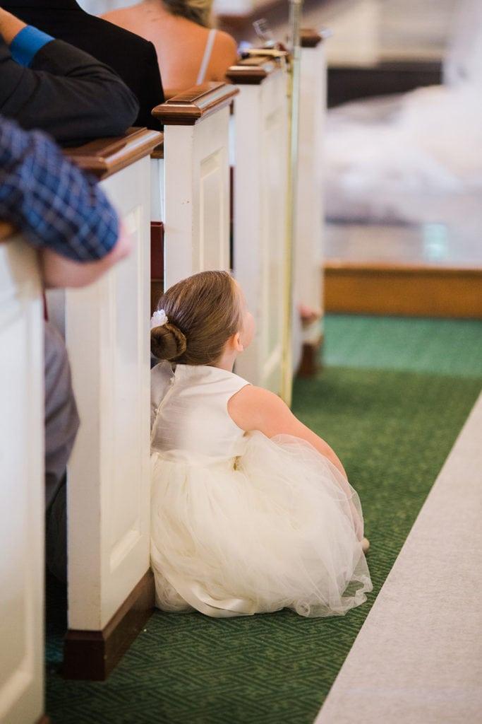 Flower girl sitting during Fox Chapel wedding ceremony