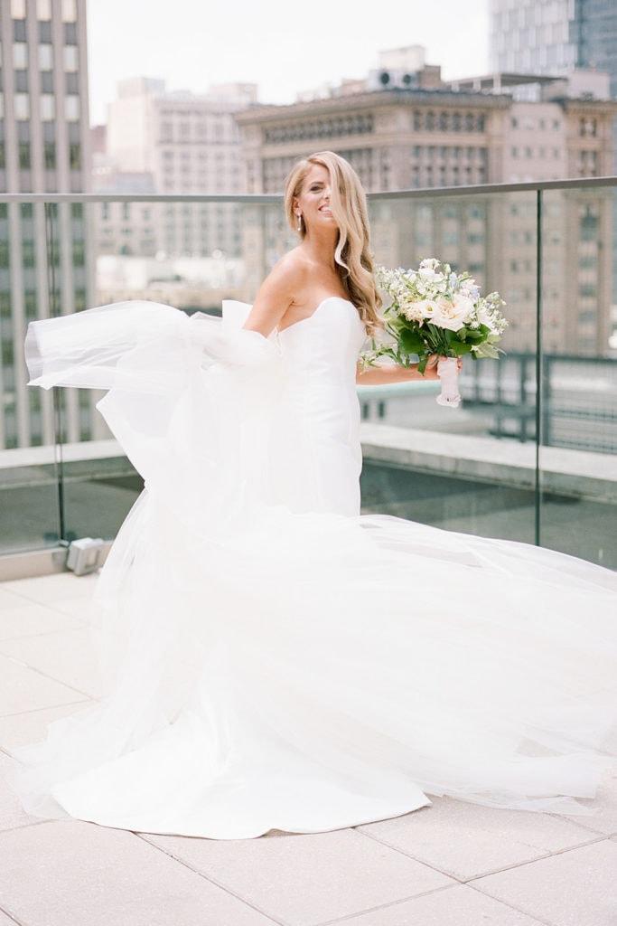 Bride twirling in Bridal Beginning wedding dresson Hotel Monaco rooftop