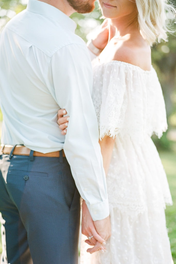 Close up of couple holding hands: styled in blue engagement session