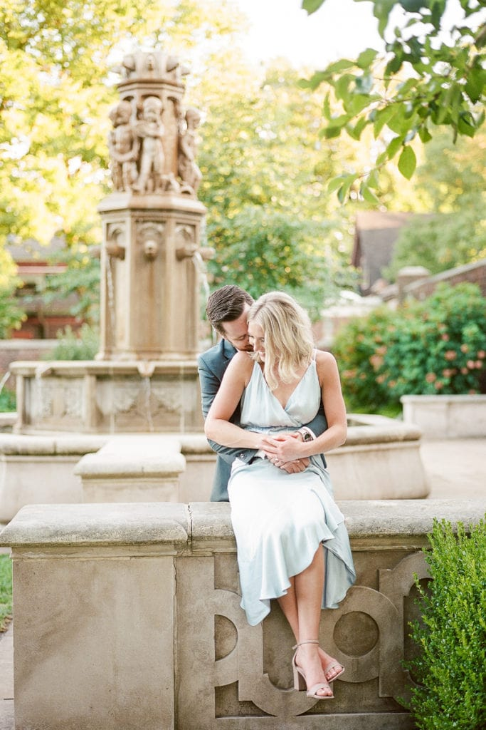 Couple cuddling while sitting in front of a stone fountain: Styled blu engagement session walled garden