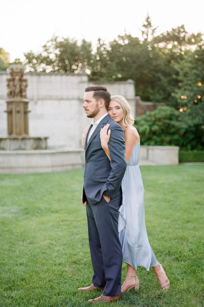 Couple posing in the grass in front of stone fountain styled in blue