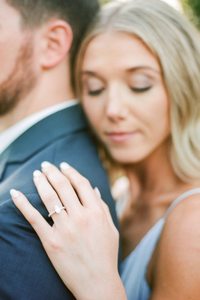 Close up of oval engagement ring on bride during their styled in blue engagement session