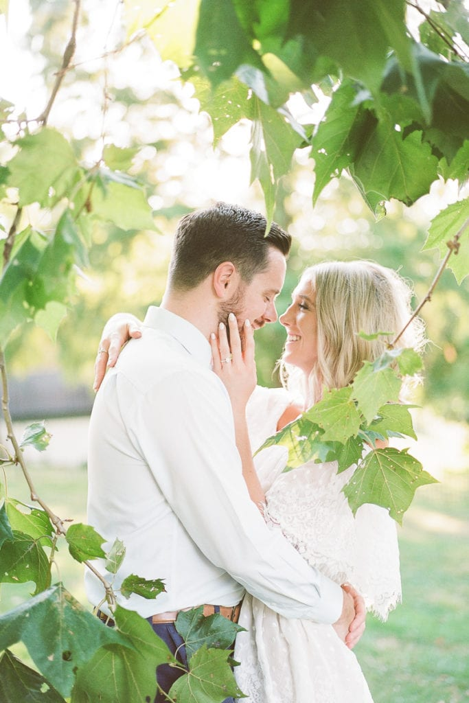 Couple sharing a sweet moment among the tress and leaves during their sun-kissed engagement session
