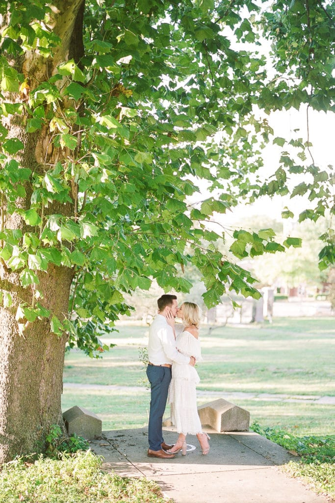 Couple standing under a large tree kissing:Styled in Blue Engagement Session at the Walled Garden at Mellon Park
