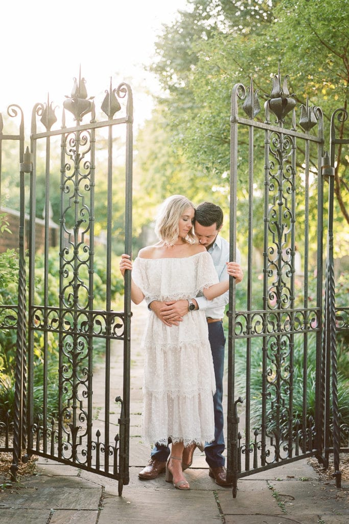 Bride wearing white show me your mumu ruffled dress standing with her groom in front of a wrought iron gate: styled in blue engagement session at the walled garden