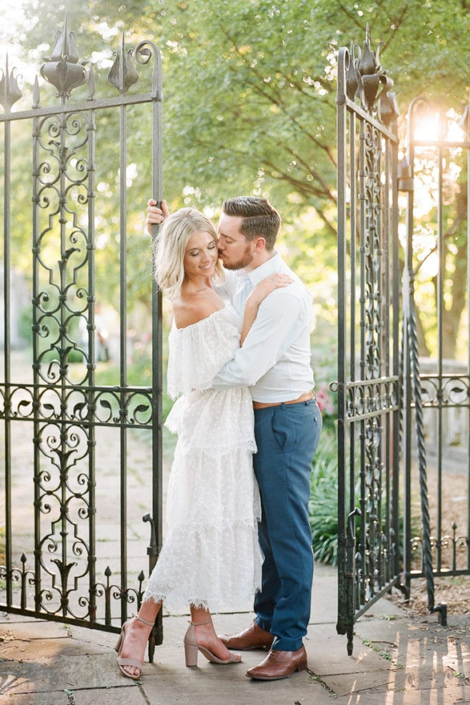Groom kissing his bride on the cheek in front of an iron gate