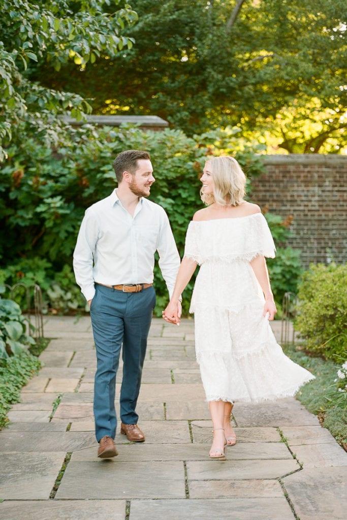 Couple walking and holding hands through the garden of Mellon Park