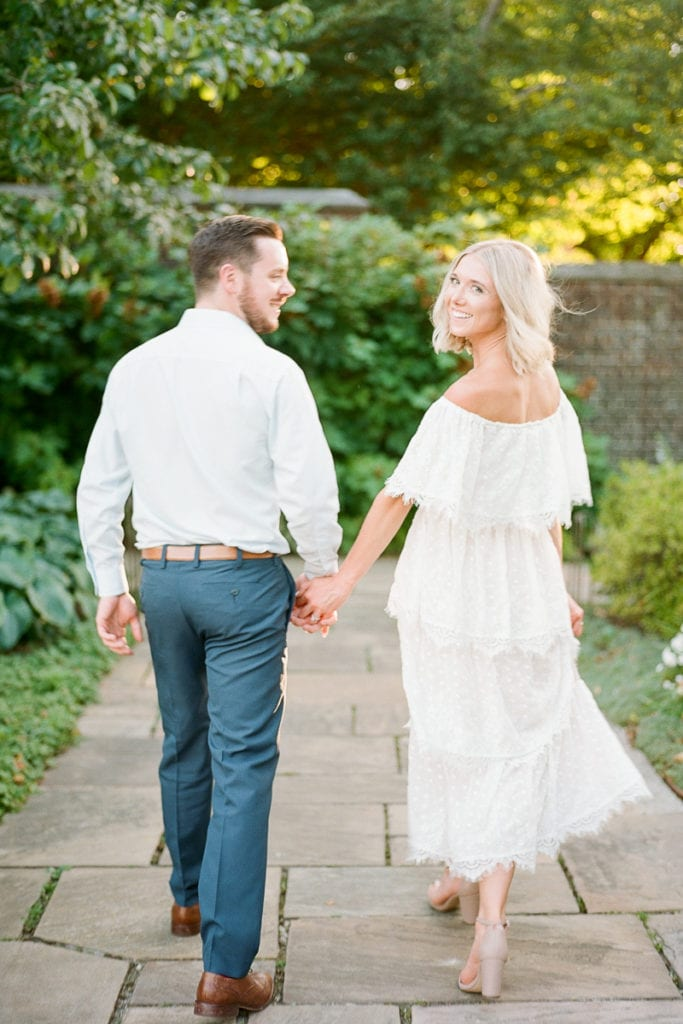 Couple walking away holding hands and bride looking over her shoulder in a show me your mumu dress