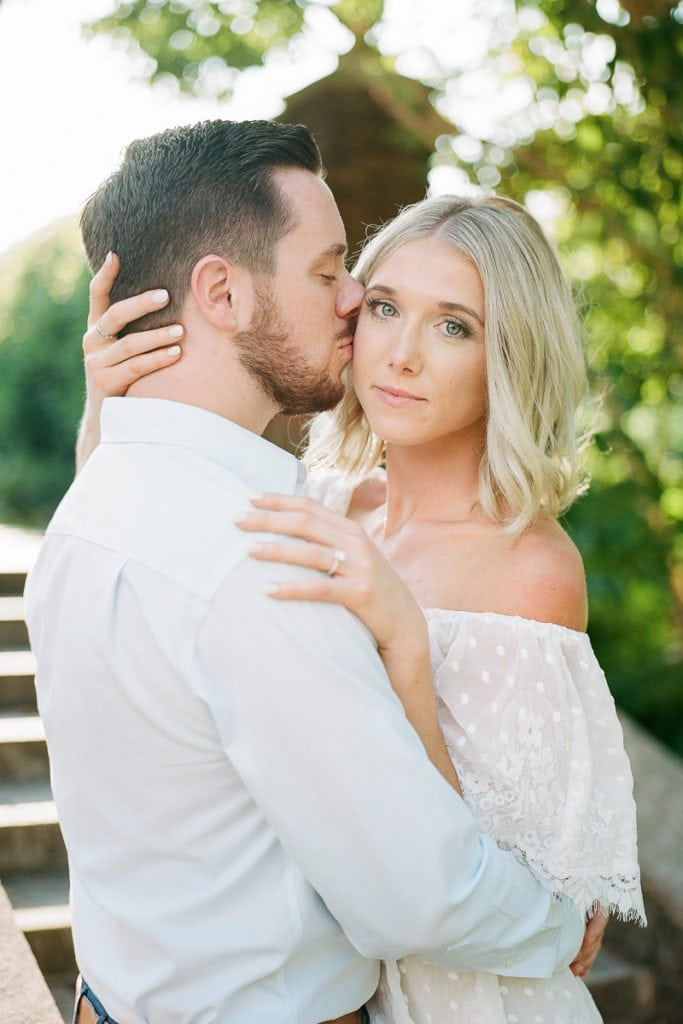 Bride with blue eyes and blonde hair wearing show me your mumu white ruffled dress posing for photos with her groom