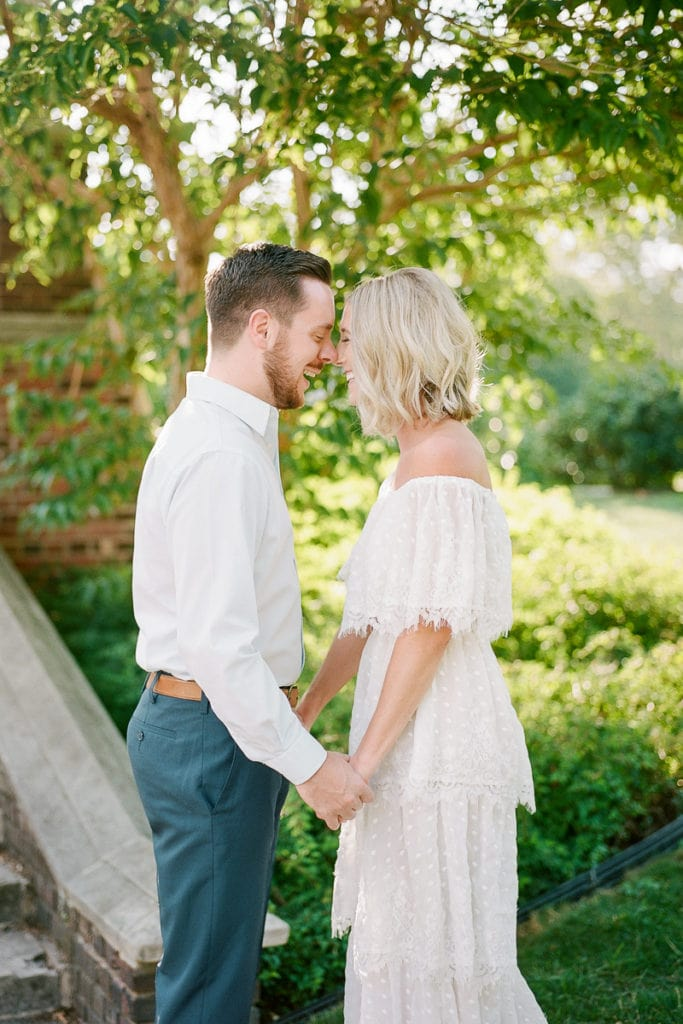 Couple laughing and rubbing roses during their engagement session