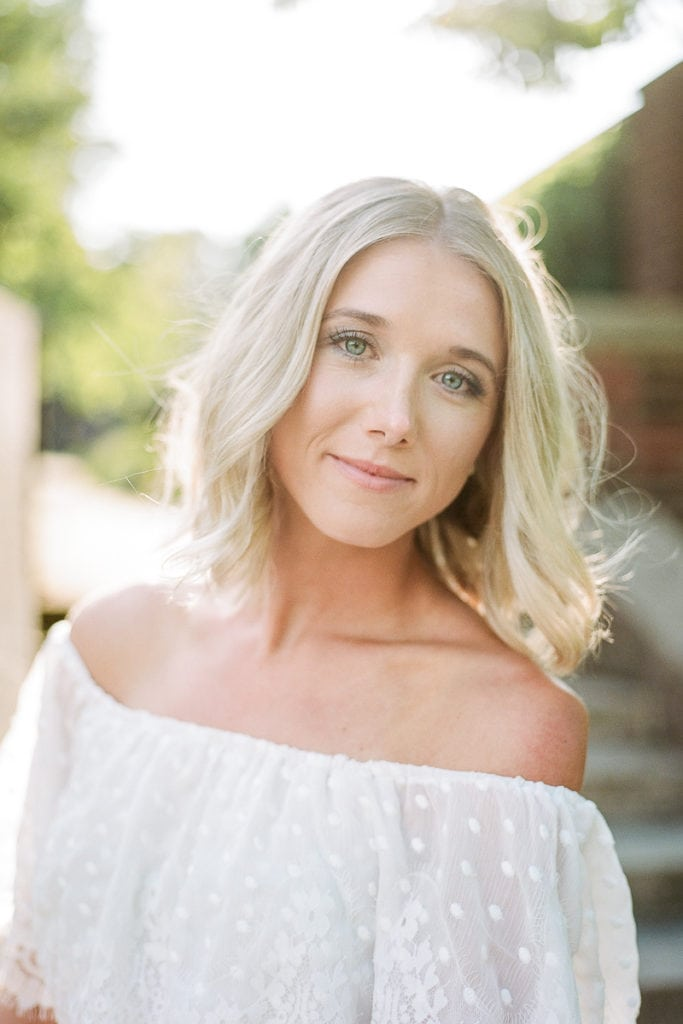Bride smiling and looking into the camera with bright blue eyes and blond hair