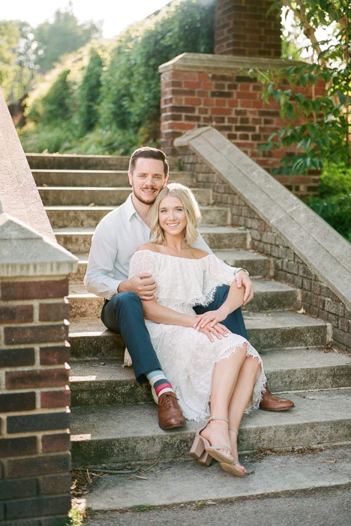 Couple sitting on stone steps smiling during their engagement session