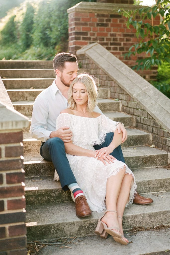 Couple sitting on stone stairs together: styled in blue engagement session