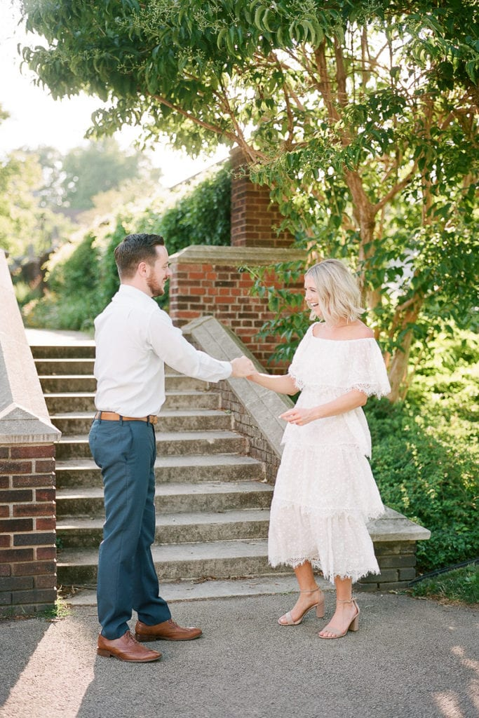 Couple laughing and dancing during their engagement session styled in blue