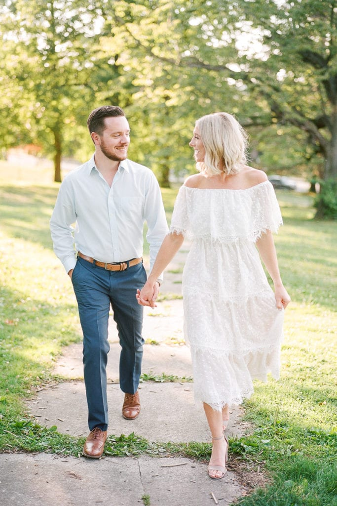 Bride and groom walking through mellon park wearing blue and white: styled in blue engagement session at the walled garden mellon park