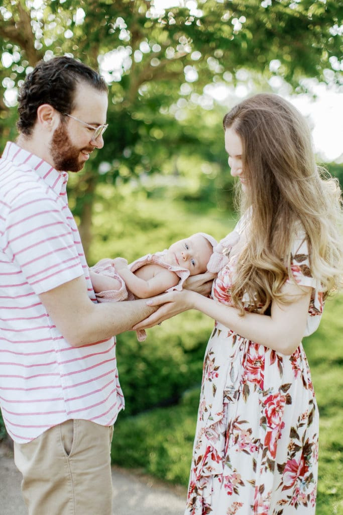 parents holding their newborn in between them in an english garden: outdoor newborn session